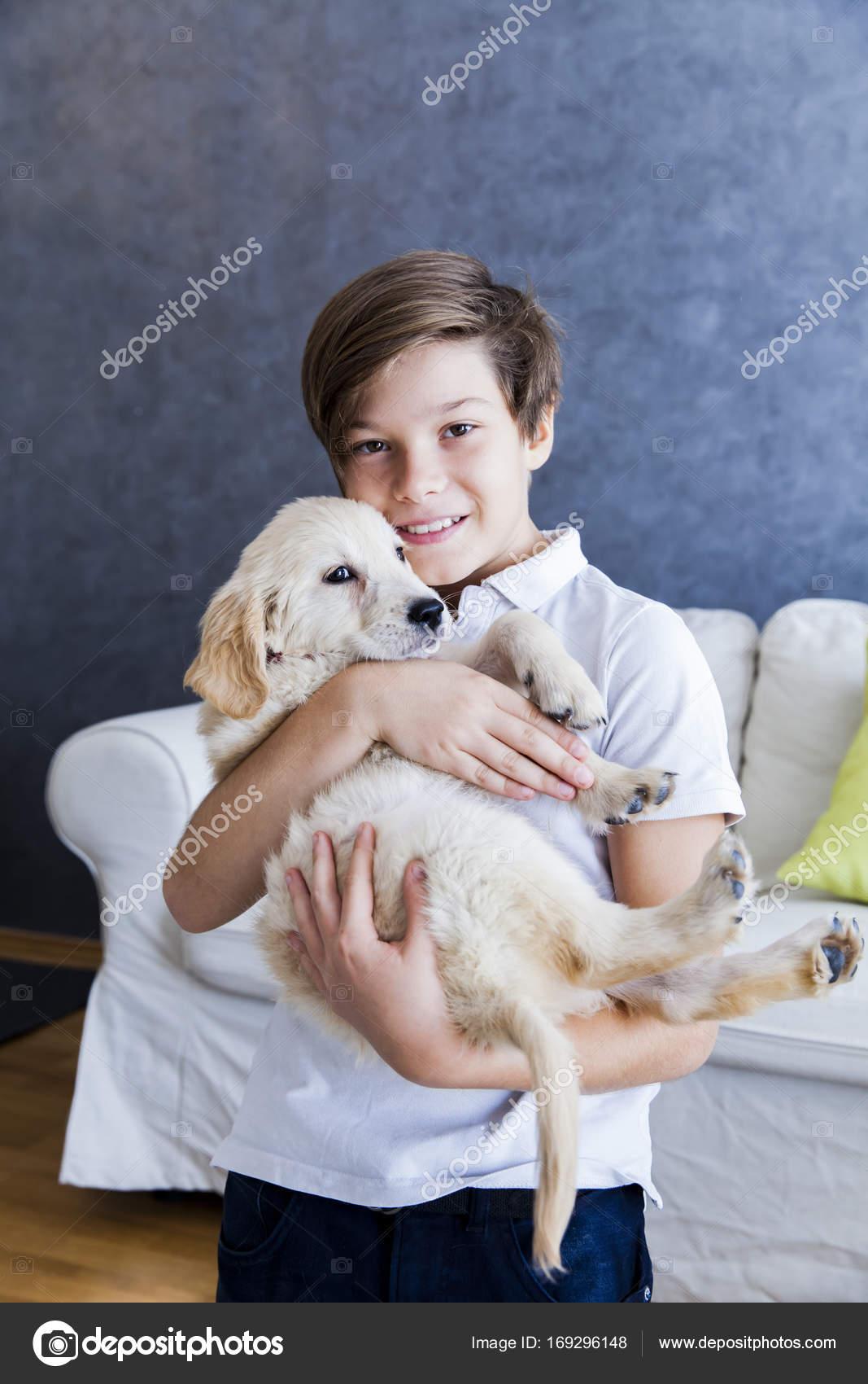 Chico lindo teen con perro retriever de bebé en la habitación– Imagen de  Archivo