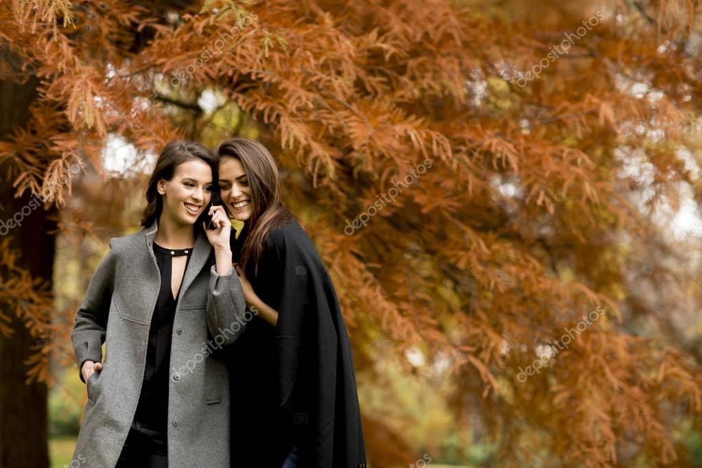 Two pretty young women using mobile phone