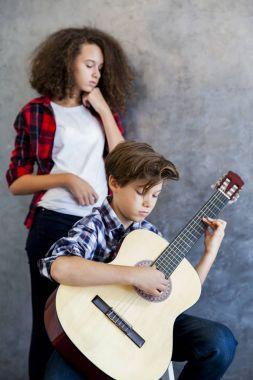Boy playing guitar while girl listening