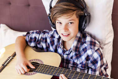 Teenage boy playing acoustic guitar in bed