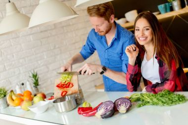 Lovely young couple preparing healthy meal in the modern kitchen
