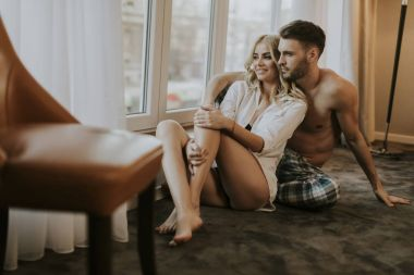 Loving couple sitting on the floor in the room by the window