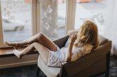 Fotografie Mladá žena pózuje v prádlo u okna v pokoji