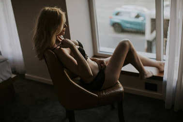 Young woman posing in lingerie by window in the room