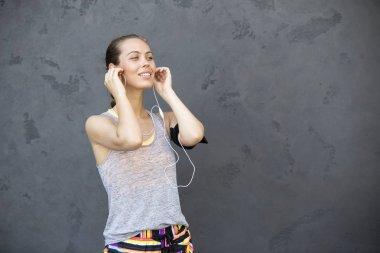 Portrait of woman taking break from jogging by the wall