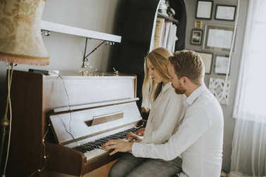 Loving couple playing piano in the room at home
