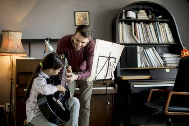 Cute little girl with guitar teacher in the room at home