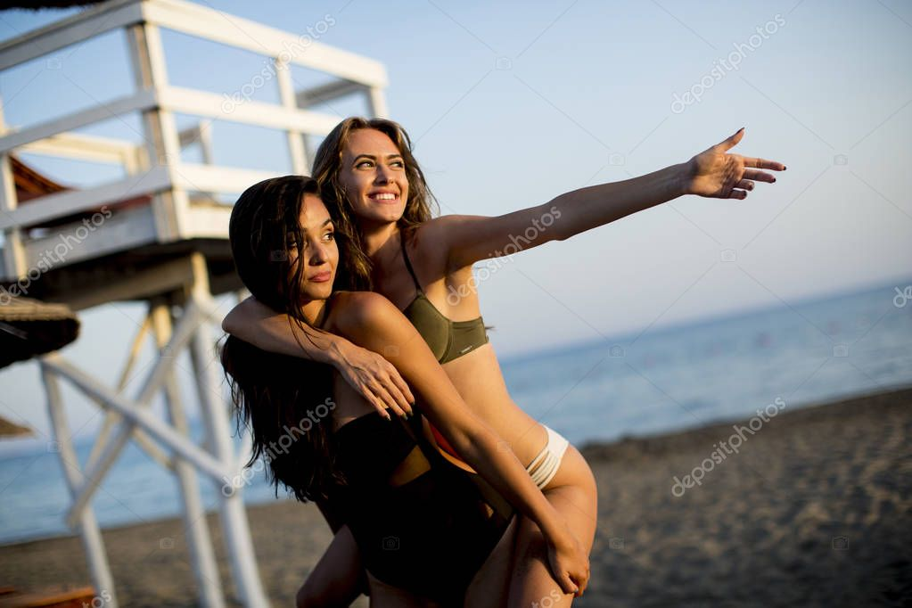 Pretty young women having fun on the beach at summer