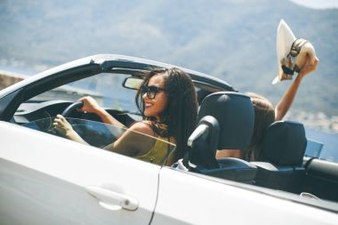 Two happy friends in white cabriolet car driving everywhere and looking for freedom and fun