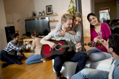 Happy friends playing guitar and listening to music at home