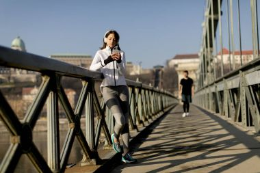 Woman on the bridge making a pause and listen music after the exercise
