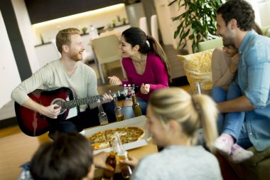 Group of young people having pizza party in the room