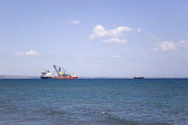 Cargo ships on the horizon of blue  sea