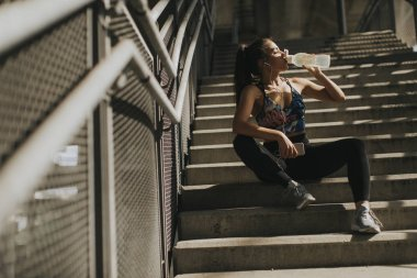 Portrait of pretty young female runner resting on stairs