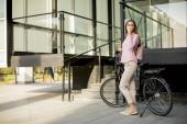 Krásná mladá cyklistka pije kávu z poháru u elektrického kola v městském prostředí