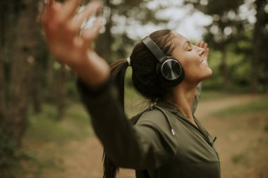 Pretty young woman with earphones preading her arms in the forest because she enjoys training outside