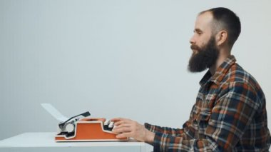 Hipster man typing with a red vintage typewriter