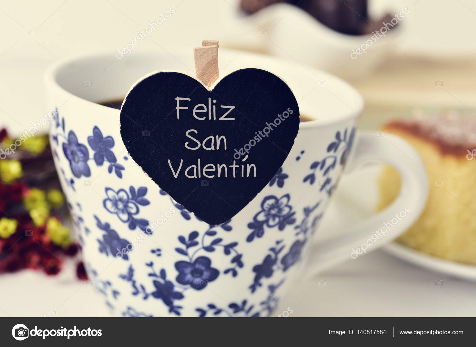 Closeup Of A Heart Shaped Signboard With The Text Feliz San Valentin, Happy  Valentines Day Written In Spanish, In A Cup Of Coffee, On A Table Set For  ...