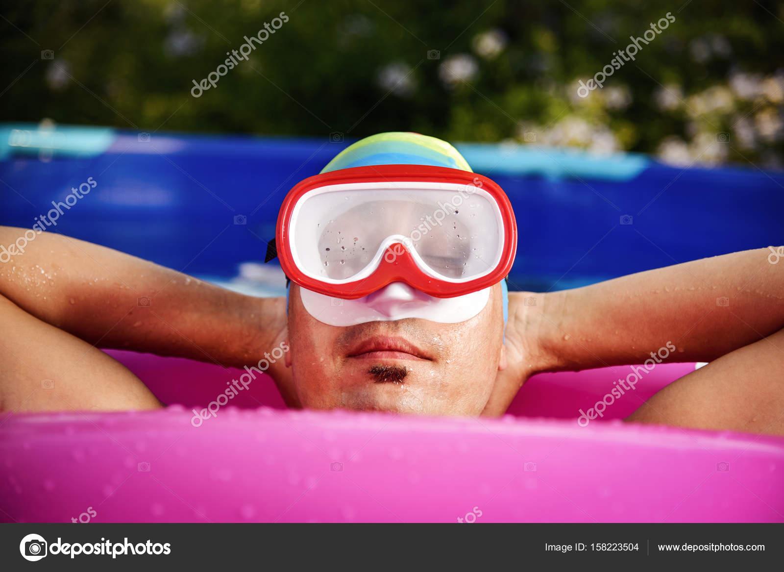 Gros plan d un jeune homme de race blanche portant un masque de plongée, un  bonnet de bain et un anneau de bain rose vif relaxant dans une piscine  portable ... ccd71d267b3
