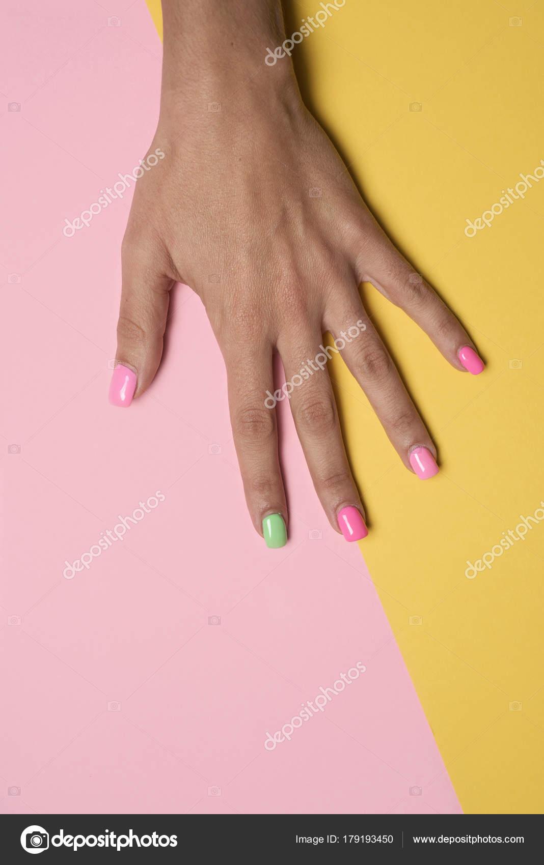 Ręka Kobiety Z Jej Paznokcie Pomalowane Różowy I Zielony Zdjęcie