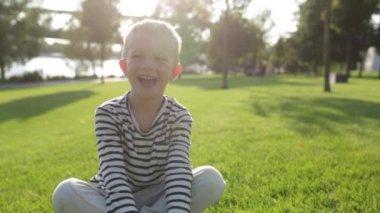Cute beautiful happy little boy smiling, sitting on grass