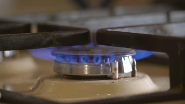 Osvětlené plyn Close-Up modré plameny zahřívá kovový rošt plynový sporák