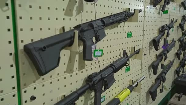 Automatic Rifles at Arms Exhibition. Automatic Weapons Hanging on the White Wall in Neat Rows