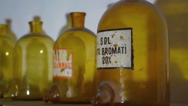 Barattoli di vetro di grandi dimensioni per chimica medica. Bottiglie in farmacia. In piedi su uno scaffale polveroso nel seminterrato