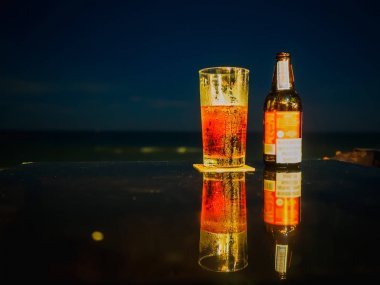 Bottle and glass of beer on the table at the beach during night