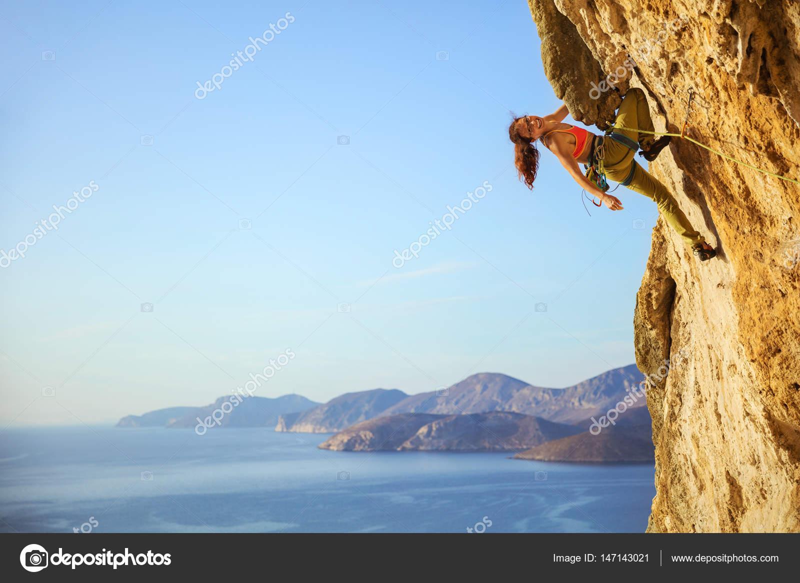 female rock climber climbing on seaside steep cliff Stock