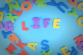 Fotografie The word Life is laid out in multicolored letters. Beautiful inscription on a blue background.
