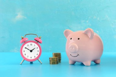 Piggy bank on a turquoise background, next to a small pink alarm clock and two stacks of coins.