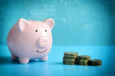 Piggy bank on a blue background. Three stacks of coins are reduced in order. The symbol is the accumulation and conservation of money.