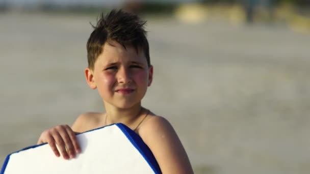 Cute primary school boy surfer posing with a board .