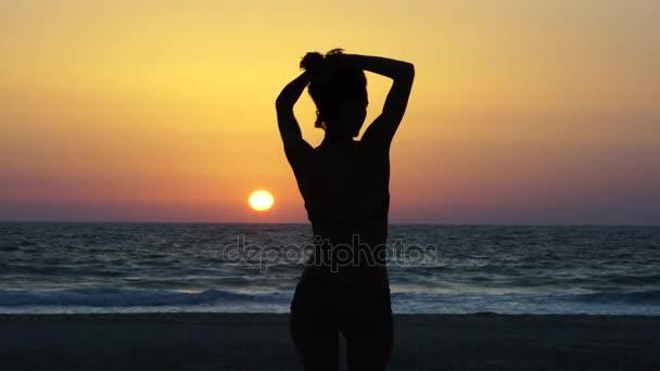 Silueta Jang elegantní žena pózuje před slunce nízko visící.