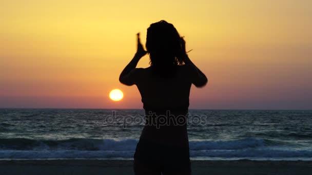 Sziluettjét yang elegáns nő előtt a nap alacsonyan lógó pózol.