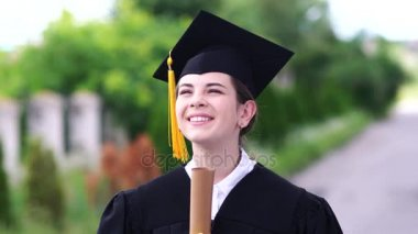 Outdoor scene of beautiful female graduating student dressed in cup and gown.