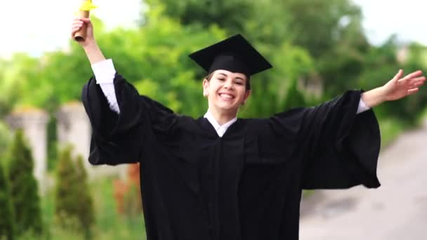 The scene of beautiful female graduating student dressed in cup and gown jumping up. Slow motion.Europe.