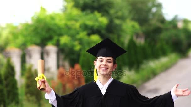 Venkovní scéna krásná studentka absolvování oblečený v poháru a šaty vyskočil.