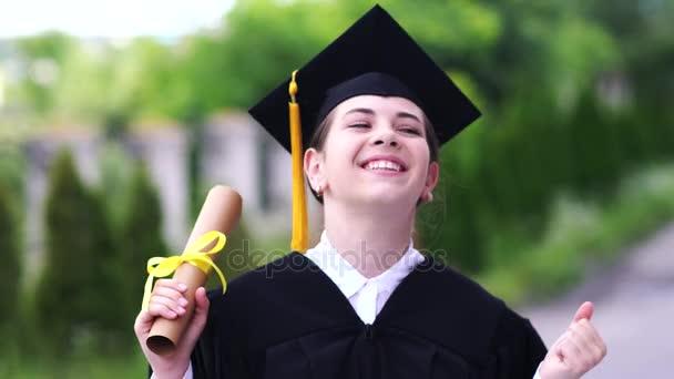 Venkovní scéna krásné maturitní studentky oblečené v šálku a šatech.