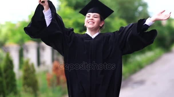 Outdoor scene of beautiful female graduating student dressed in cup and gown jumping up.