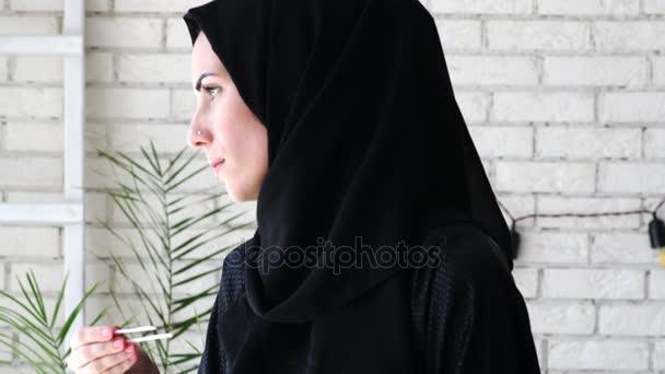 Mladá arabská žena držící pozitivní těhotenský test.