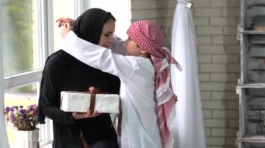 Arabic mother and son posing with present indoor.