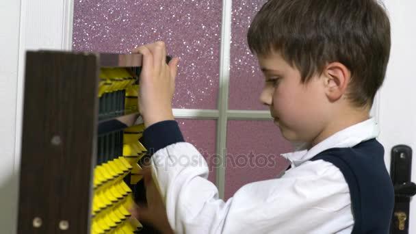 Iskola fiú számlálás a abacus egy osztályteremben. Oktatás
