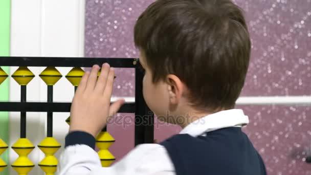 Iskola fiú öltözött, mint tanár tartja abacus, egy osztályteremben.