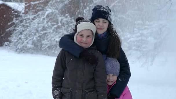 Portrét malé batole dívka v zimní oblečení s padající sněhové koule.