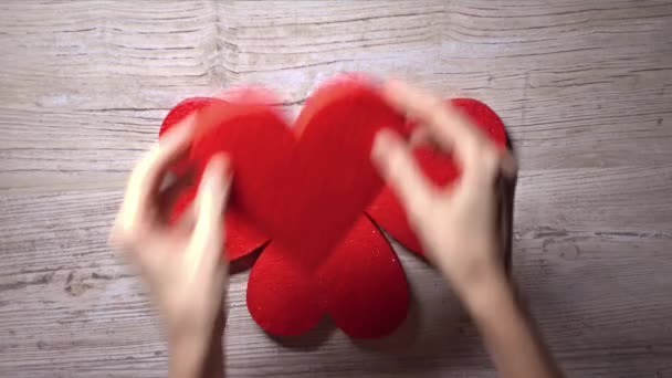 Girl taking four red hearts from a wooden table, top view. Care, love, Valentines day concepts. 4K video