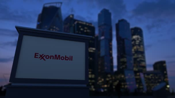 Street signage board with ExxonMobil logo in the evening  Blurred business  district skyscrapers background  Editorial 4K clip