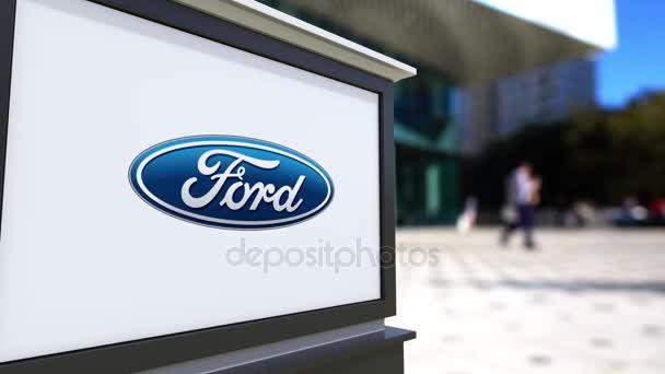Pouliční nápisy desky s logem Ford Motor Company. Centrum rozmazané office a chodící lidé pozadí. Úvodník 4k 3d vykreslování
