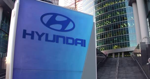 Pouliční nápisy deska s logem Hyundai Motor Company. Moderní kancelářské centrum mrakodrap a schody pozadí. Úvodník 4k 3d vykreslování
